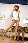 Playful gal with perfect body dressing in her silky flesh-colored pantyhose