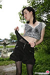 Salacious chick in barely black pantyhose taking time for posing outdoors
