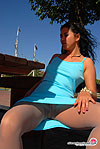 Pretty brunette in blue gown and natural hose showing nyloned pink close-up