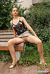 Upskirt gal in barely visible hose makes sexy spreads showing slit outdoors