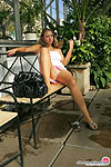 Frisky babe flashing the briefs of her extra shiny pantyhose in the street