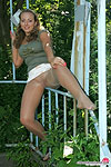 Upskirt babe in shiny pantyhose showing she's wearing no panties underneath